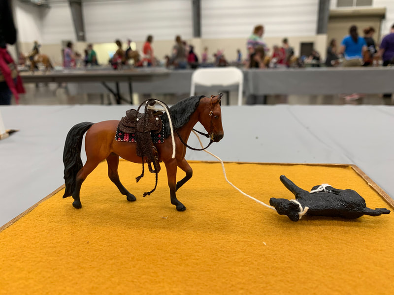 A mini artist resin morgan horse competing in calf roping at The Jennifer Show 2019.